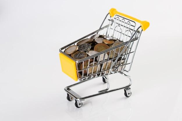 Negócios e financeiro, conceito de compras com carrinho de compras cheio de moedas múltiplas. fundo branco.