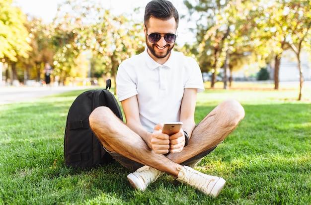 Negócios e hipster elegante em uma camisa branca, sentado no gramado do parque e trabalhando em um smartphone