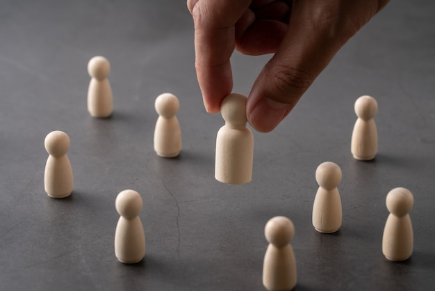 Negócios e rh conceito global de quebra-cabeça de madeira para liderança e equipe com peg boneca e mão