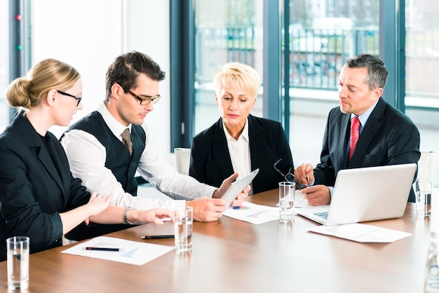 Negócios - em uma reunião no escritório, os empresários ou advogados da equipe discutem um documento no laptop