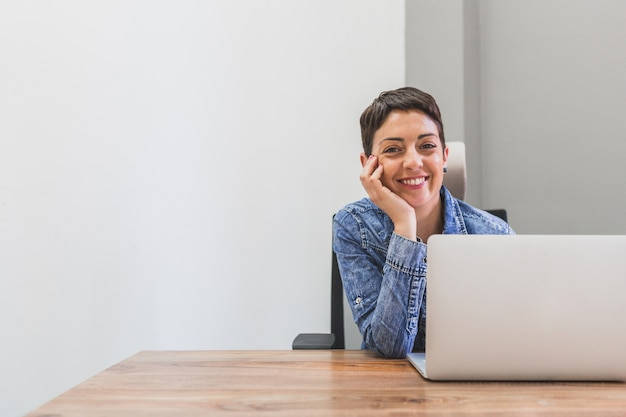 Negócios feliz que levanta ao lado de seu laptop