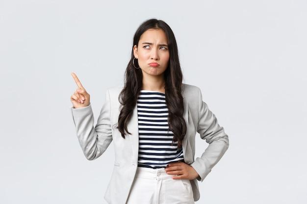 Negócios, finanças e emprego, conceito de empresárias de sucesso feminino. gerente de escritório cético e hesitante, empresária asiática de terno tendo dúvidas, sorrindo maliciosamente e apontando para o canto superior esquerdo