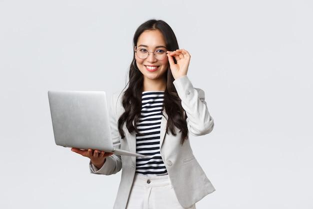 Negócios, finanças e emprego, conceito de empresárias de sucesso feminino. mulher de negócios asiática confiante e sorridente, trabalhadora de escritório em terno branco e óculos usando laptop, ajuda os clientes