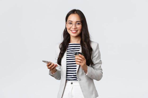 Negócios, finanças e emprego, conceito de empresárias de sucesso feminino. mulher de negócios asiática profissional de óculos, almoçando, tomando café para viagem e usando o telefone celular
