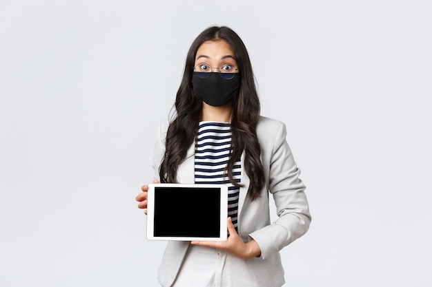 Negócios, finanças e emprego, conceito de prevenção de vírus e distanciamento social covid-19. mulher de negócios asiática empolgada com máscara facial e óculos arregalam os olhos de surpresa, mostrando a tela do tablet digital