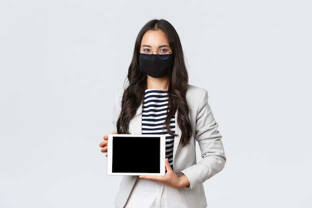 Negócios, finanças e emprego, conceito de prevenção de vírus e distanciamento social covid-19. trabalhador de escritório asiática mostrando apresentação na reunião com tela de tablet digital, usar máscara facial
