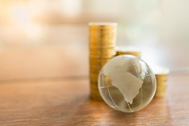 Negócios globais e conceito financeiro. feche acima da mini bola do mundo de cristal claro com a pilha de moedas de ouro na tabela de madeira e copie o espaço.
