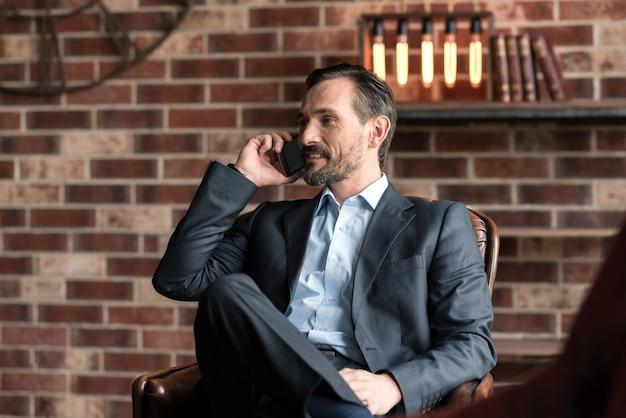 Negócios. homem bonito e alegre sentado na poltrona e falando ao telefone enquanto trabalhava em seu escritório