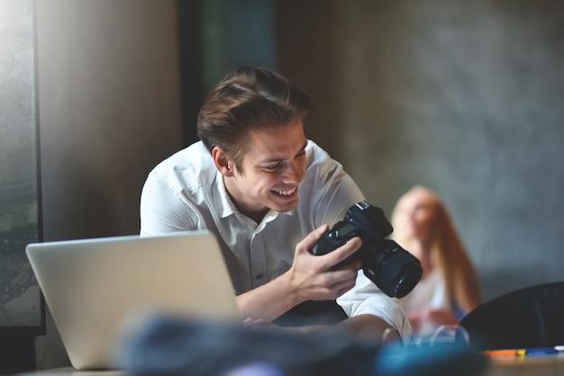 Negócios, inicialização e o conceito de pessoas - um feliz fotógrafo, designer, trabalhador de escritório masculino criativo verificando as imagens em sua câmera.