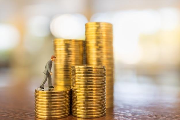 Negócios, investimento em dinheiro e conceito de planejamento. feche acima da figura diminuta dos povos do homem de negócios que anda em cima da pilha de moedas de ouro na tabela de madeira com cópia sapce.