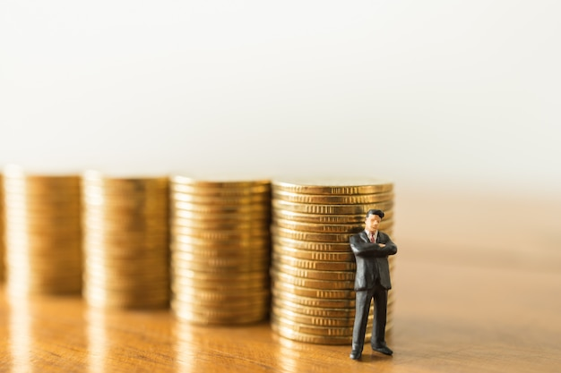 Negócios, investimento em dinheiro e conceito de planejamento. feche acima da figura diminuta dos povos do homem de negócios que está com a pilha de moedas de ouro na tabela de madeira com cópia sapce.