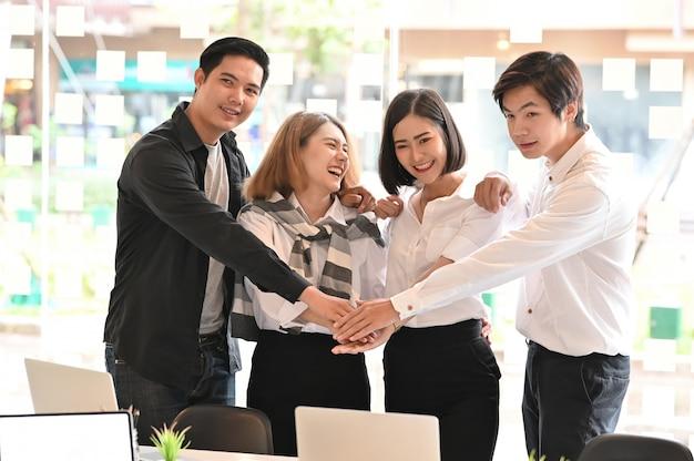 Negócios juntos, quatro jovens empresários com confiança e motivação relaxam no escritório moderno.