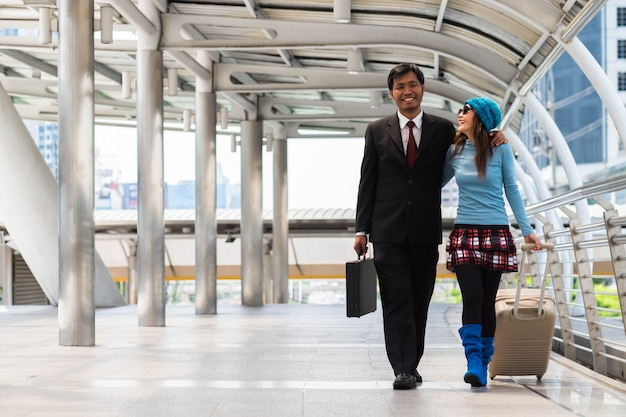 Negócios masculino e feminino espera viagens bagagem andar pelo caminho de passageiros.
