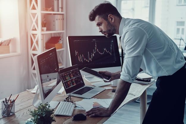 Negócios modernos. jovem empresário pensativo em trajes formais, analisando dados usando tablet digital enquanto trabalha no escritório