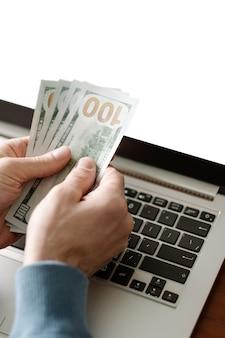 Negócios on-line remoto trabalhando ganham dinheiro em casa, homem com as mãos segurando dinheiro