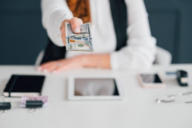 Negócios online com salário em dinheiro. feminino, estendendo notas de dólar. ganhar dinheiro na internet.