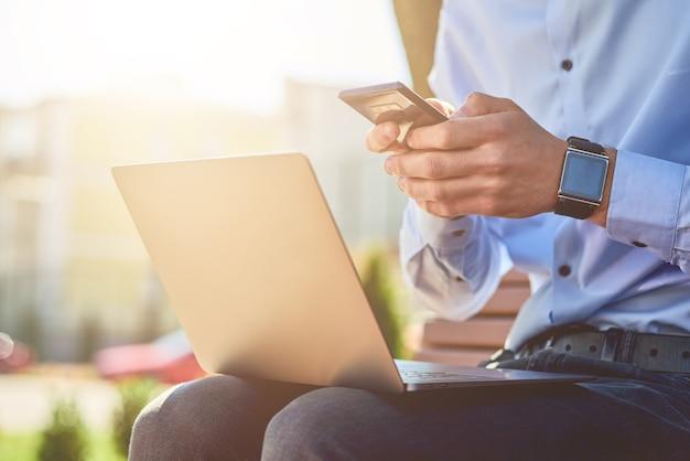 Negócios online cortaram a foto de um empresário usando smartphone e laptop enquanto está sentado no
