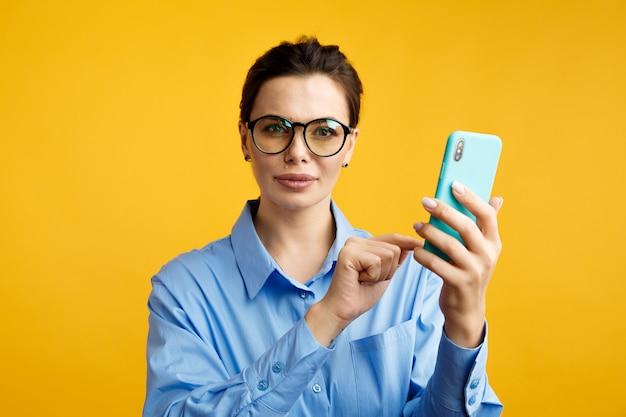 Negócios online. mulher de óculos usando telefone isolado sobre o fundo amarelo.