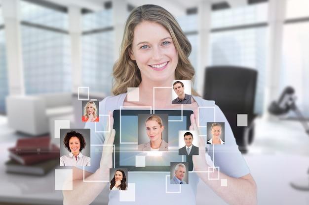 Negócios que mostra seu tablet sorrindo com um aplicativo virtual