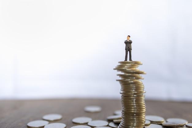 Negócios, risco, investimento e conceito de economia. feche acima da figura diminuta dos povos do homem de negócios que está sobre a pilha instável de moedas com espaço da cópia.