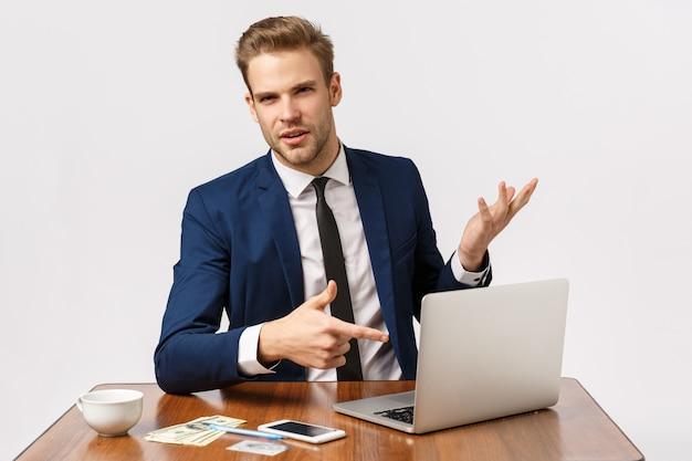 Negócios, sucesso e conceito corporativo. bonito jovem empresário discutir empresa, apontando a tela do laptop como funcionário de consultoria, na xícara de café de mesa, dinheiro, cartão de crédito e smartphone