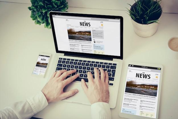 Negócios, tecnologia e conceito de design responsivo: mãos escrevendo em um laptop com o site de notícias de telefone e tablet