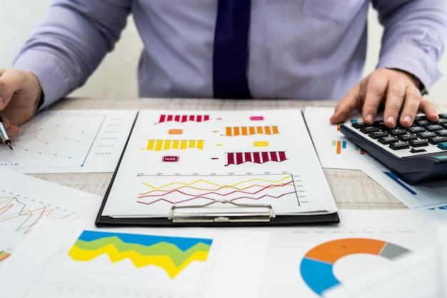 Negócios, tecnologia, finanças e conceito de ocupação de escritório - jovem empresário com diagrama gráfico de laptop e documentos no escritório