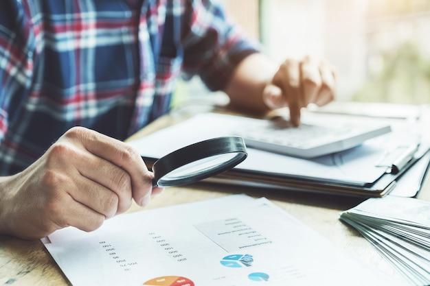 Negócios usando a ampliação para rever o balanço anual com o uso de calculadora e computador portátil