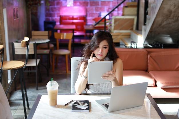 Negócios vendendo on-line, jovem mulher asiática em vestido casual trabalham no tablet e computador
