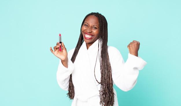 Negra afro-americana adulta vestindo roupão de banho e segurando um batom
