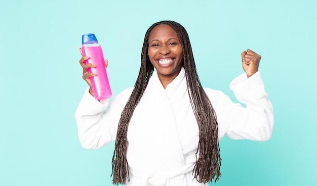 Negra afro-americana adulta vestindo roupão de banho e segurando um xampu