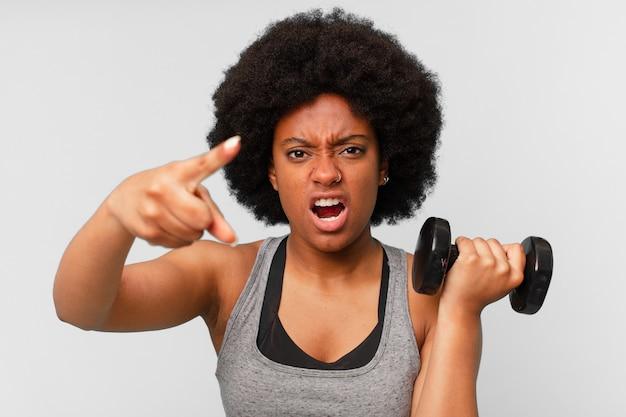 Negra afro fitness com um haltere
