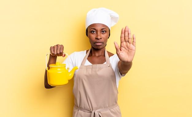 Negra chef afro olhando sério, severo, descontente e com raiva, mostrando a palma da mão aberta, fazendo gesto de parada. conceito de bule