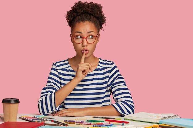 Negra silenciosa faz gesto de shush, tem cabelos cacheados penteados em coque, olha secretamente de lado, usa macacão listrado, pede para não fazer barulho, tem inspiração para desenhar, modelos sobre parede rosa