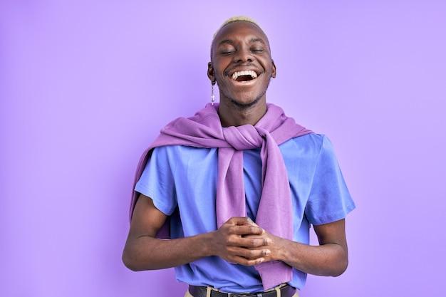 Negro engraçado rindo após uma piada isolada em estúdio, rindo de olhos fechados, em roupas casuais coloridas