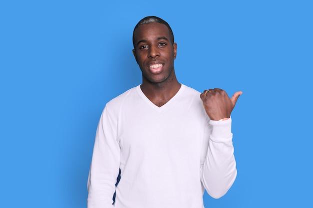 Negro sorridente cara apontando o polegar de lado no espaço em branco para texto de pé sobre fundo azul.