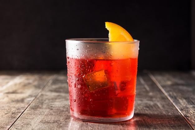 Negroni cocktail com pedaço de laranja em vidro na mesa de madeira