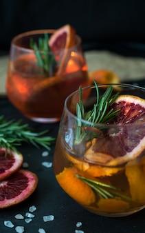 Negroni cocktail no preto servido com uma fatia de laranja e alecrim.