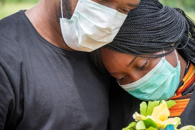 Negros em luto pelos perdidos devido ao coronavírus, usando máscaras faciais, demonstrando apoio mútuo