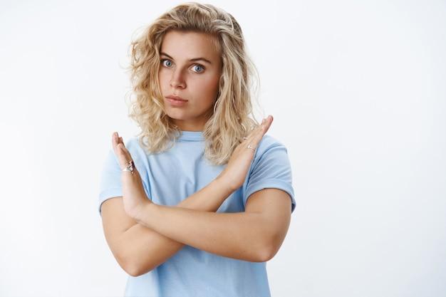 Nem pense nisso. retrato de mulher loira, séria e autoritária, de aparência séria, com corte de cabelo encaracolado curto e olhos azuis expressando desacordo, mostrando gesto cruzado na proibição
