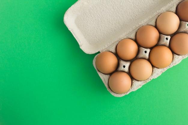Nenhum conceito de embalagem plástica. ovos de galinha marrom na caixa de papelão na superfície verde. vista do topo. copie o espaço.