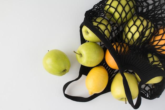 Nenhum conceito de saco plástico. malha de sacola preta com frutas diferentes na mesa branca. vista do topo. copie o espaço.