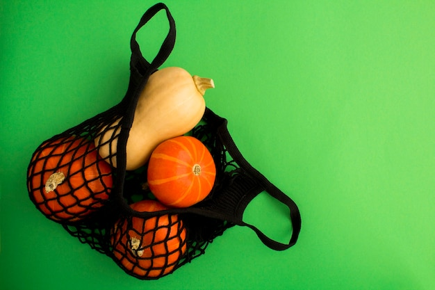 Nenhum conceito de saco plástico. saco de compras de malha preta com abóbora no fundo verde