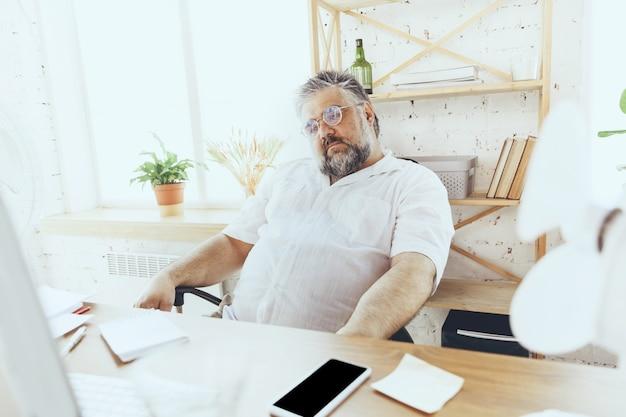 Nenhum gerente de empresário resgatando no escritório com computador e ventilador, esfriando a sensação de calor