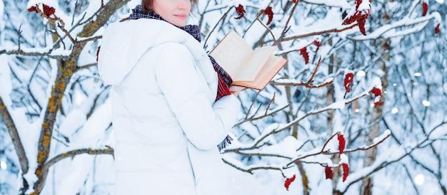 Nenhum retrato de nome de uma garota encantadora que lê um livro na floresta de inverno. conceito de natal, celebrações de inverno, passeios na floresta, férias. mídia mista