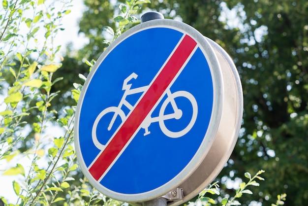 Nenhum sinal de trânsito ciclismo contra arbustos verdes