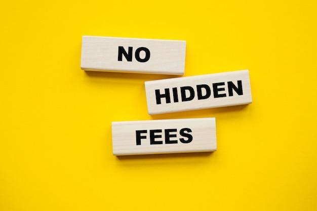 Nenhuma inscrição de taxas ocultas em cubos, caneta amarela sobre um fundo amarelo. uma solução brilhante para negócios, finanças, conceito de marketing