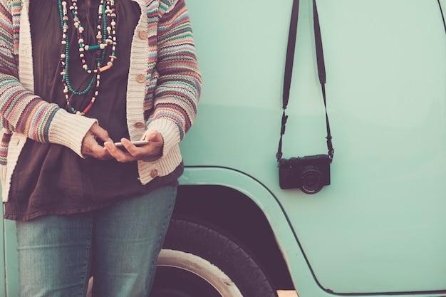 Nenhuma mulher com rosto reconhecível usando tecnologia de telefone, mensagens com van vintage azul e câmera retro na lateral - imagem do conceito de viagens e hippie