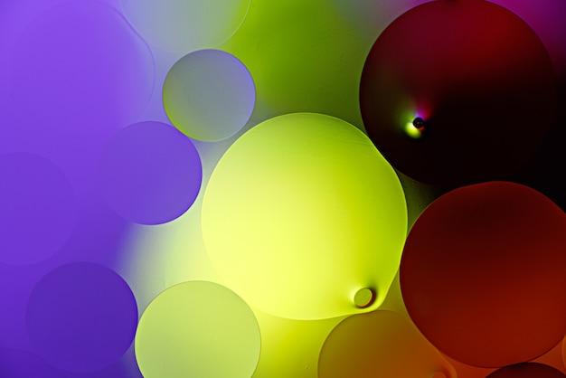 Néon brilhante brilhante borbulha bolas de gotículas de óleo na superfície da água, fundo abstrato