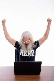 Nerd barbudo sênior parecendo motivado ao usar o laptop